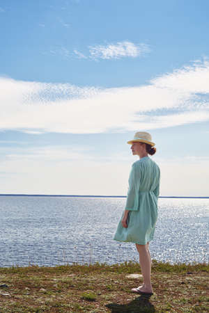 Mid adult woman standing by sea in green dress,Eggergrund,Sweden
