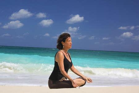 Mature woman in lotus position on beach,Paradise Island,Nassau,Bahamas