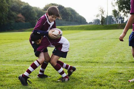 Teenage schoolboy rugby team practicing defence