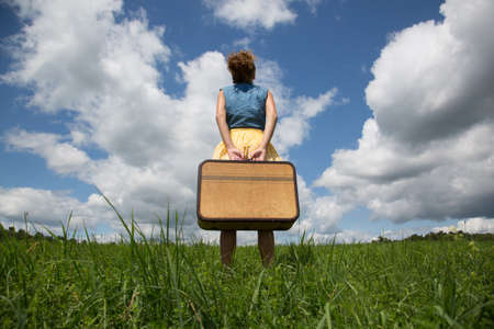 Teenage girl holding suitcase in field LANG_EVOIMAGES