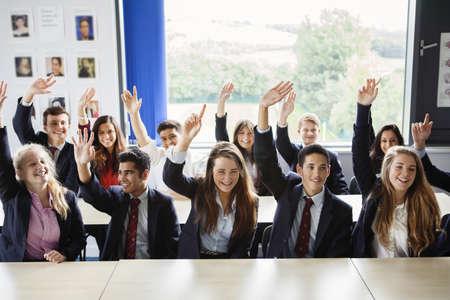 north western european descent: Teenage schoolchildren with hands raised in classroom LANG_EVOIMAGES
