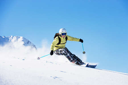 exhilarating: Female skiing down mountainside LANG_EVOIMAGES