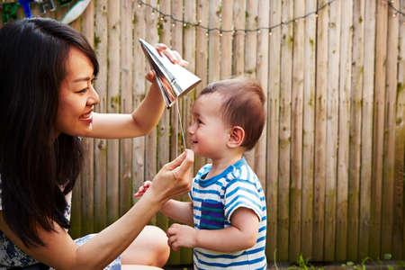 Mother putting party hat on baby boy