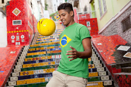 sleeve: Young man wearing Brazil top doing keepy uppys in front of the Escadaria Selaron steps in Rio de Janiero,Brazil LANG_EVOIMAGES