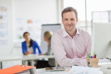 Mature businessman working at desk in office,portrait LANG_EVOIMAGES