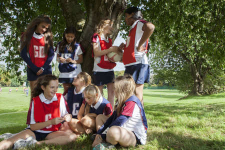 low self esteem: Teenage schoolgirl netball team taking a break