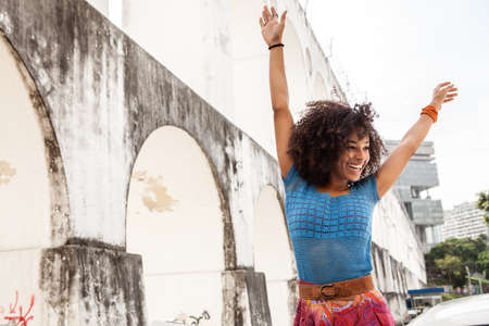 Young woman standing in front of Carioca Aqueduct with arms raised,Rio,Brazil LANG_EVOIMAGES