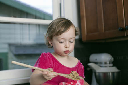 Girl with wooden spoon of cookie dough LANG_EVOIMAGES