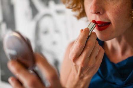 Close up of woman applying lipstick
