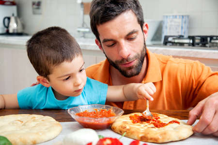 pizza base: Father and son making homemade pizza