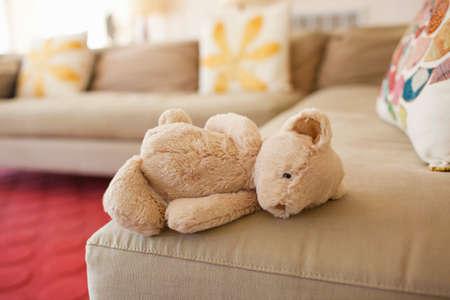 Teddy bear lying on couch