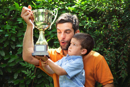 Father and son holding trophy
