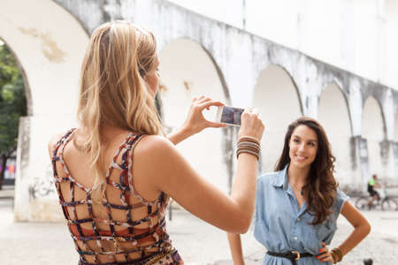 hands free phone: Young woman taking photograph of friend in front of Carioca Aqueduct,Rio de Janeiro,Brazil