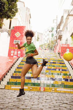 Young woman doing keepy uppys in front of the Escadaria Selaron steps in Rio de Janiero,Brazil