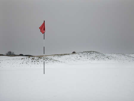 Golf flagpole on snow covered course