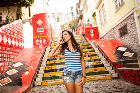 Young woman on phonecall in front of the Escadaria Selaron steps in Rio de Janiero,Brazil