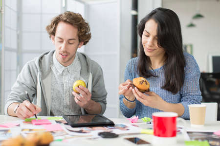 Mid adult woman and young man eating muffin in creative office meeting