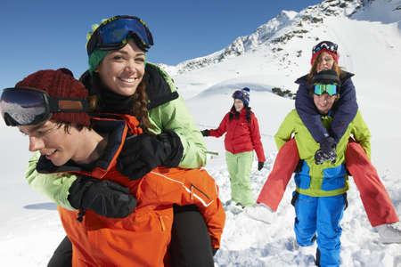 ski walking: Men giving women piggy backs in snow,Kuhtai,Austria