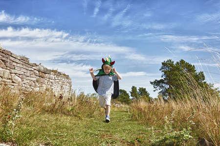 Boy wearing green cape running along grass,Eggergrund,Sweden
