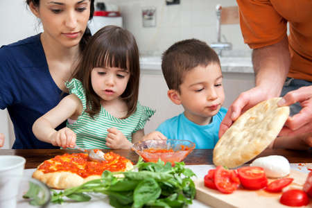 pizza base: Family making homemade pizza