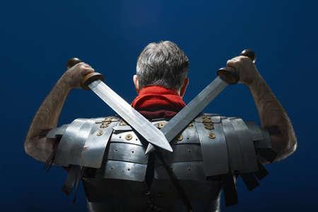 Rear view studio portrait of roman soldier with swords LANG_EVOIMAGES