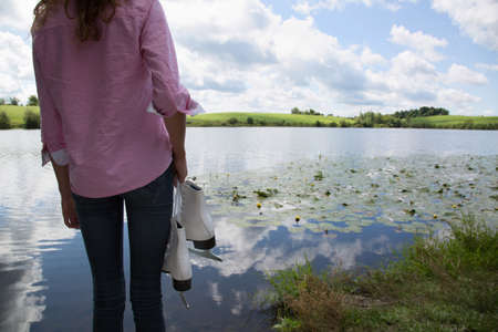 Teenage girl next to lake holding ice skates