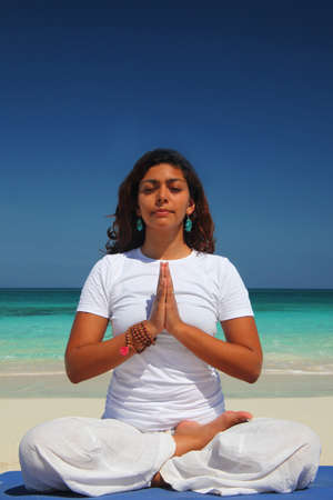 living idyll: Young woman doing yoga lotus position,Paradise Island,Nassau,Bahamas LANG_EVOIMAGES