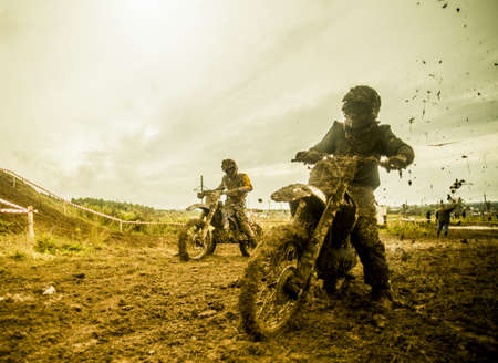 Two boys racing motorcycles at motocross