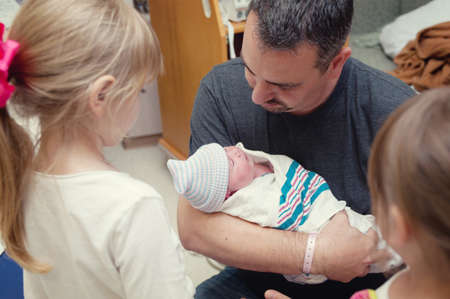 Father cradling newborn baby girl with two older sisters LANG_EVOIMAGES