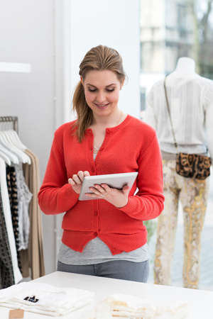 salespeople: Young female using digital tablet in fashion shop