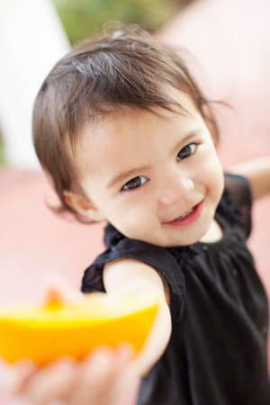 Close up of baby girl holding out slice of orange LANG_EVOIMAGES