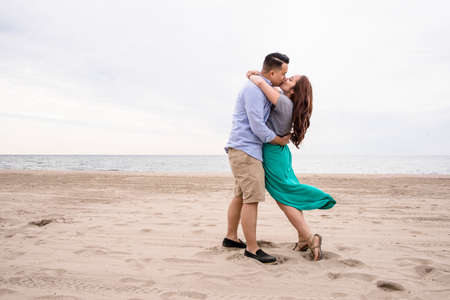 getting out: Young couple hugging at beach LANG_EVOIMAGES