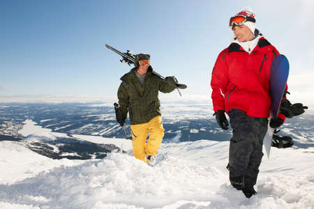 Snowboarders and skiers carrying equipment to the top of mountain LANG_EVOIMAGES