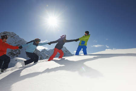 Friends pulling each other uphill in snow,Kuhtai,Austria LANG_EVOIMAGES