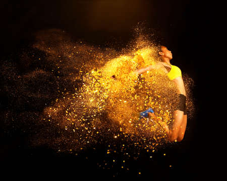 athletic wear: Young woman mid air emerging from yellow powder explosion