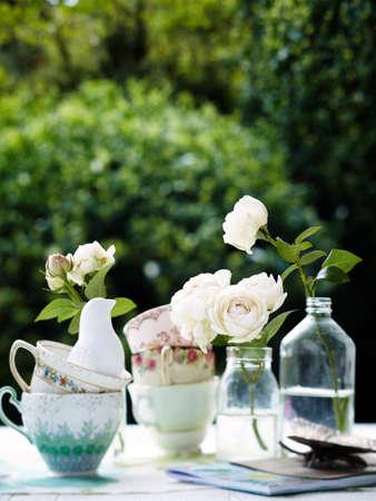 vintage: Flowers in vintage bottles with teacups