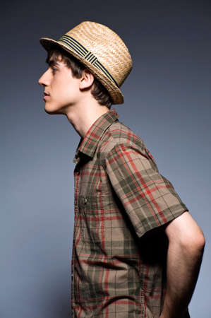 Young man wearing hat and short sleeved shirt, profile