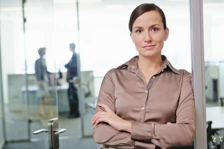 Mid adult woman standing in office with arms crossed