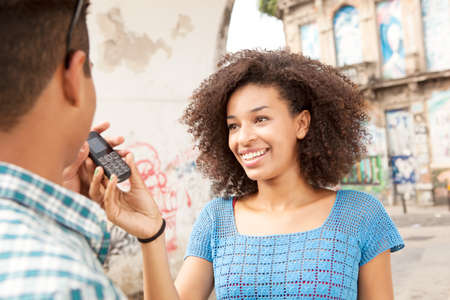 brazilian ethnicity: Young woman handing mobile phone to man LANG_EVOIMAGES