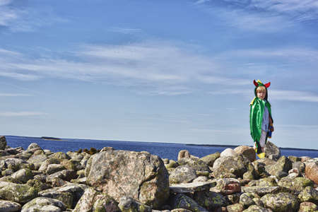 Boy wearing green cape standing on stone wall,Eggergrund,Sweden LANG_EVOIMAGES