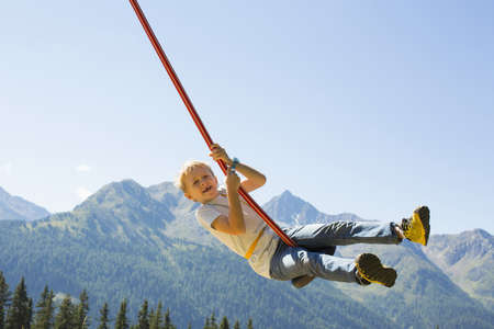 living idyll: Boy playing on swing,Tyrol,Austria