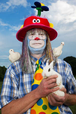 Portrait of clown holding a rabbit and with doves on shoulders LANG_EVOIMAGES