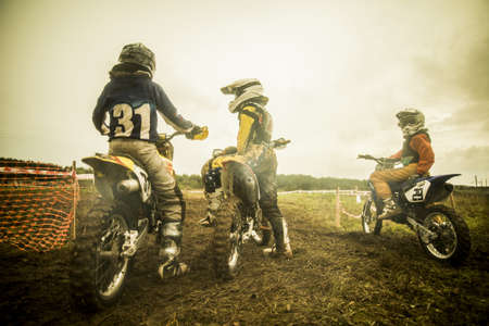 Young man and boys on motorcycles at motocross