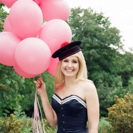 Woman wearing bustier and hat holding balloons