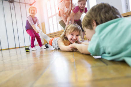 Children lying on fronts playing pulling game