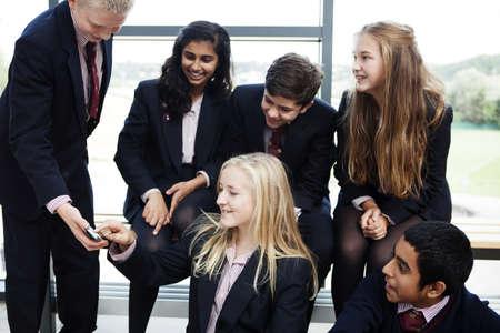low self esteem: Group of teenage schoolchildren looking at mobile phone