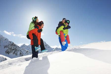 exerting: Friends giving piggy backs in snow,Kuhtai,Austria