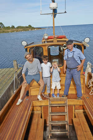 Father and two sons with fisherman on boat,Eggergrund,Sweden