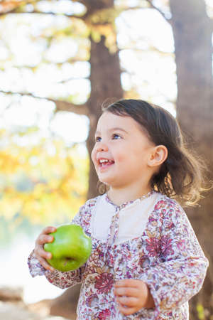 joyous: Child with toothy smile holding green apple