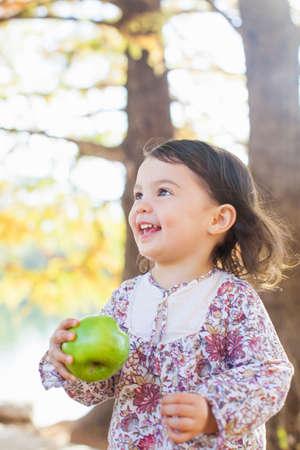 pelo castaño claro: Niño con sonrisa dientes sosteniendo la manzana verde